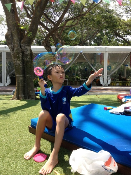 This boy made a wise decision by sitting here and playing with bubbles when he was too tired to run in on the water play area