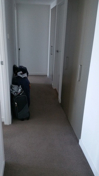 The hallway which would take us to the master bedroom on the left and laundry room and second bathroom on the right