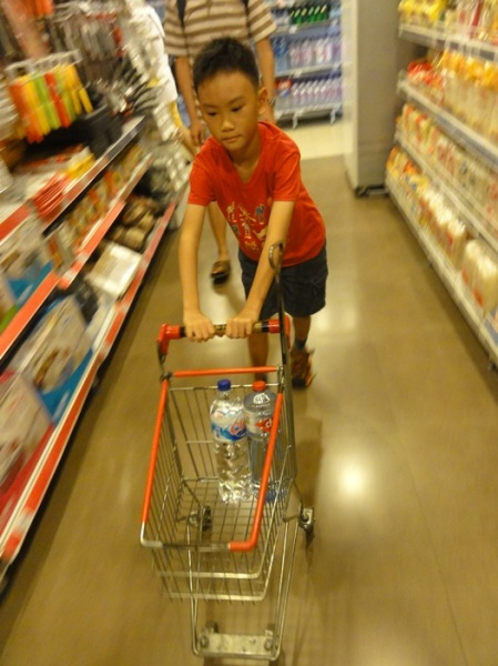He was very happy pushing this small trolley around the supermarket