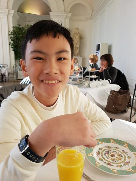 A happy boy with his orange juice
